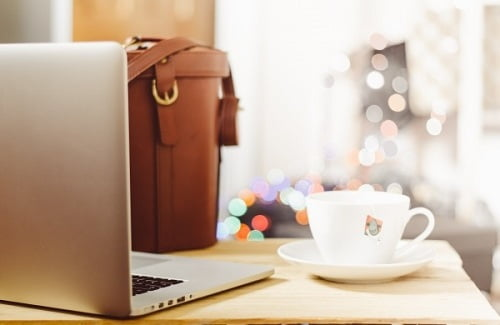 laptop-handbag-and-coffee-cup-on-wooden-table